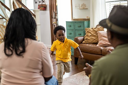 Child running in a living to towards his parents