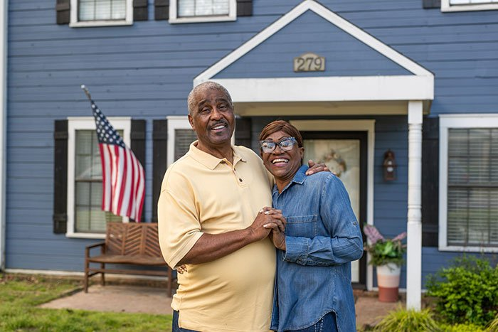 http://Couple%20with%20arms%20around%20eachother%20standing%20in%20front%20of%20their%20house